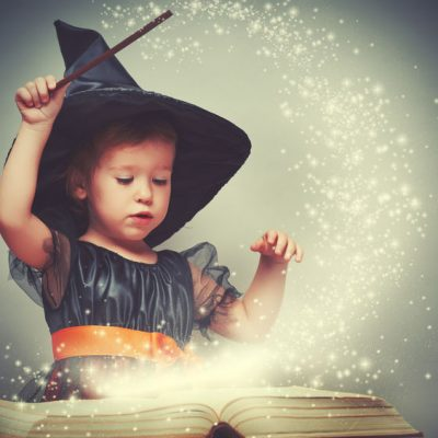 45560809 - halloween. cheerful little witch with a magic wand and glowing book conjure and laughs.