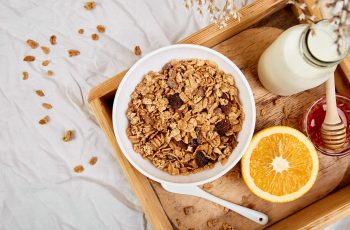 Good morning. Breakfast on white bed sheets. Muesli or granola, milk, orange  on wooden tray from above. Top view.  Flat lay. Copy space. Hotel Room Early Morning.