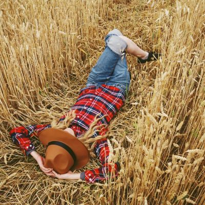 Young woman with country style is resting in a field of wheat